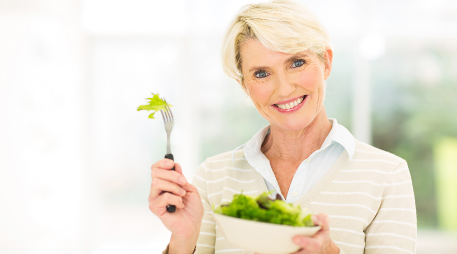 pretty middle aged woman eating vegetable salad